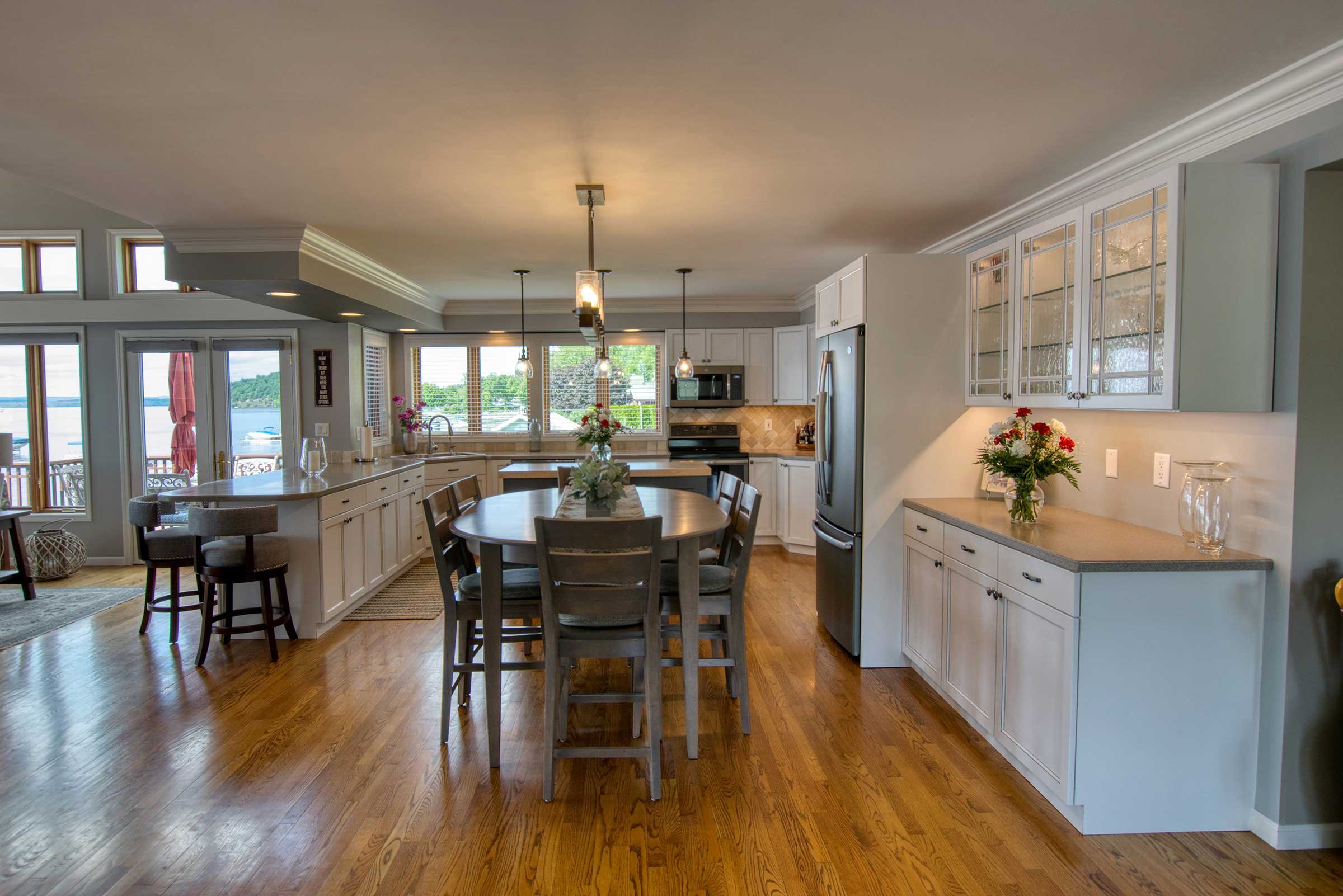 Long view from entryway through dining area into kitchen with refaced cabinets and lake view outside of windows.
